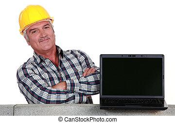 proud mason posing next to his laptop