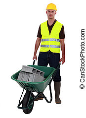 Man pushing waste material in wheelbarrow
