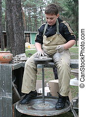 Young boy potter working with clay on wheel