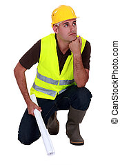 Pensive laborer crouching on white background