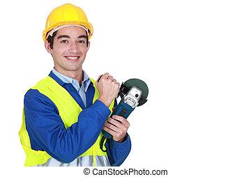 Smiling laborer holding sander