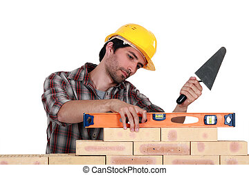 A mason using  a level to check his wall.