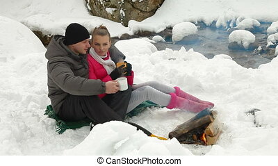 Winter Picnic In Woods By The Fire - Young Couple By The...