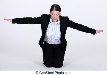 Kneeling businesswoman with arms stretched