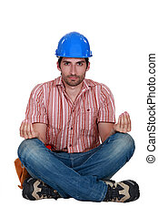 A construction worker in the lotus position.