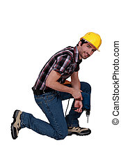 Man kneeling with drill