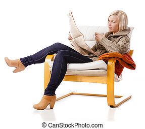 Reading the newspaper - Casual young woman sitting in cozy...