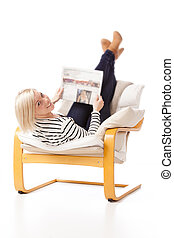 Reading the newspaper - Young woman laying in an armchair...