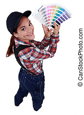 Woman holding up paint colour samples
