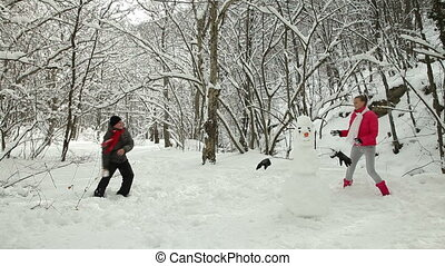 Young Couple Throwing Snowballs In Winter Forest