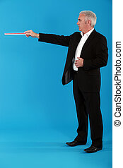 A businessman pointing with a ruler