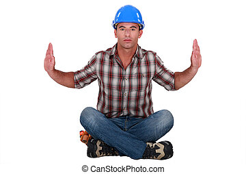 Austere tradesman leaning forward and holding up his arms