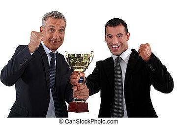 businessmen holding a golden cup
