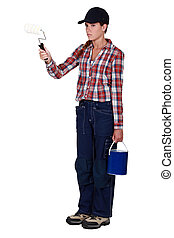 Angry tradeswoman holding a paint roller