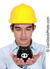 Young construction worker with piggy bank in hands