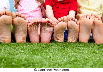 Funny feet - Happy friends sitting on the grass barefoot