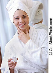 Cheerful beauty - Smiling woman in bathrobe and towel using...