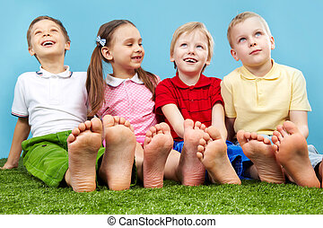 Group of kids - Happy children sitting on the lawn barefoot