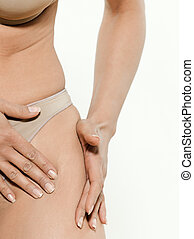 Closeup of woman showing her cellulite on the thigh in...