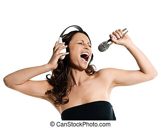 Portrait of a beautiful Asian woman with microphone and headphones singing in studio isolated on white background