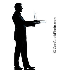 one caucasian business man computing computer laptop silhouette standing Full length in studio isolated on white background