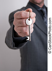 real estate agent - A real estate agent holds out the front...
