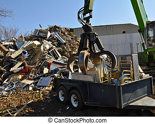 Scrap Yard - A working picker in a scap yard moving and...