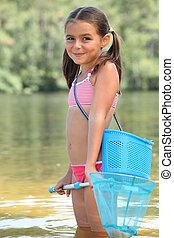 cute little girl fishing in river