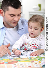 little girl colouring under dads watchful eye