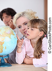 a mother is showing to her daughter some country on a globe, her husband is on the phone