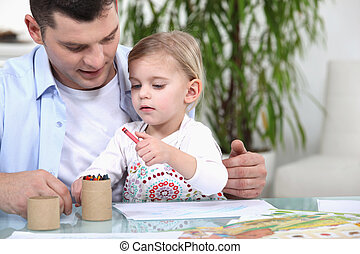 Father and daughter colouring with crayons