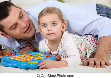 Father and daughter playing game at home