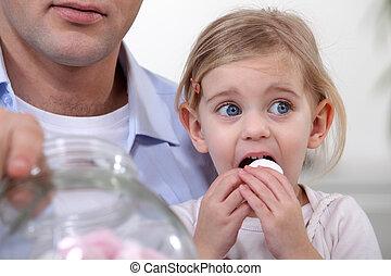 Little girl eating marshmallows