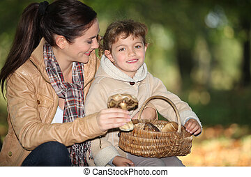 Young woman and little girl with basket of mushrooms