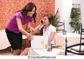 Woman looking at a laptop in a restaurant