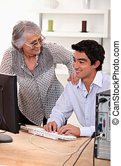 Young man using computer and happy senior woman