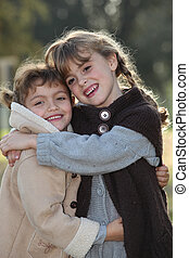 tender scene of two little girls hugging