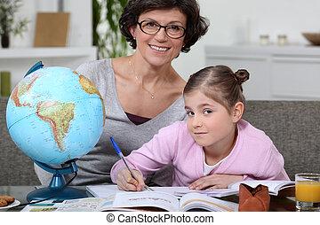 Little girl doing homework with her mom