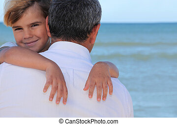 A father hugging his son on the beach.