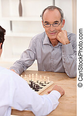 grandpa playing chess game with grandson