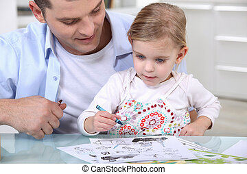 Little girl drawing with father