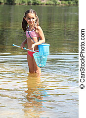 Young girl fishing with a net