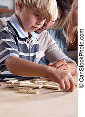 Young boy playing dominoes with his father