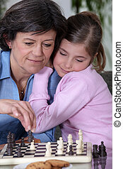 A grandmother and her granddaughter playing chess