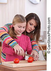 Woman showing her daughter how to cut a tomato