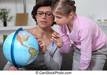 Little girl looking at a globe with her grandmother