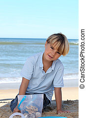 Little boy collecting starfish in a bucket on the beach