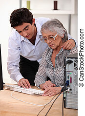 Grandson showing grandmother how to use computer