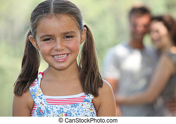 portrait of jovial little girl with parents in background