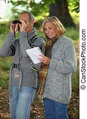 Senior woman and senior man watching through binoculars